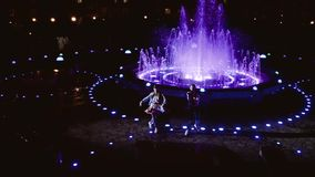 Two cheerful dancer. A guy and a girl dance at night. Dancers on the background of the fountain. stock video