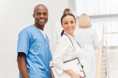 Two cheerful doctors looking over shoulder and smiling while the Stock Photography