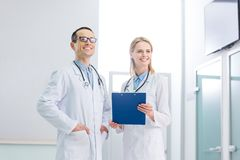 Two cheerful doctors in white coats with stethoscopes and diagnosis standing. In clinic stock photo