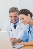 Two cheerful doctors working on a laptop Stock Images