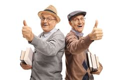 Two cheerful elderly men with books making thumb up gestures royalty free stock photo