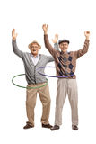Two cheerful elderly men with hula hoops Royalty Free Stock Photography