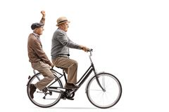 Two cheerful elderly men riding a bicycle together. Isolated on white background stock images