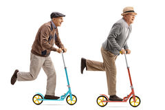 Two cheerful elderly men riding scooters Stock Photography