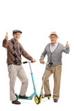 Two cheerful elderly men with scooters giving thumbs up Stock Photography