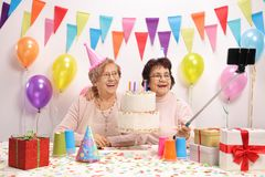 Two cheerful elderly women with party hats and a birthday cake t. Aking a selfie with a stick stock images