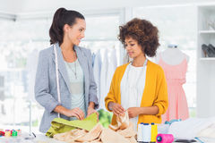 Two cheerful fashion designers touching textile Royalty Free Stock Photo
