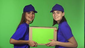 Two cheerful female delivery service workers smiling holding cardboard box stock images