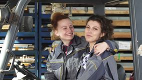 Two cheerful female factory workers hugging smiling happily to the camera. Young beautiful female factory technicians sitting in a forklift embracing laughing to stock video