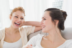 Two cheerful female friends sitting on sofa in living room Stock Images