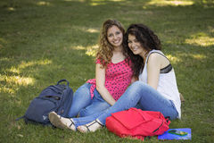 Two cheerful female friends. Smiling teenage students seating outdoor Royalty Free Stock Photo