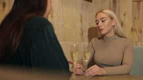 Two cheerful friends drinking champagne in the cafe. stock video