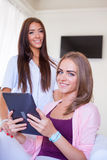 Two cheerful friends having fun and looking at mobile tablet pc. Stock Photo