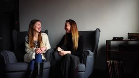 Two cheerful girlfriends chat and smile, sitting in gray chairs in stylish cafe on winter evening. stock video