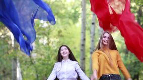 Two cheerful girlfriends girls throw up blue and red cloth on the day of nature stock footage