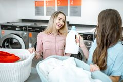 Women with detergent and clothes in the laundry. Two cheerful girlfriends sorting clothes for washing holding bottle with detergent in the self service laundry stock photography