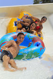 Two cheerful girls and boy drive with tube on the rafting slide Stock Photo