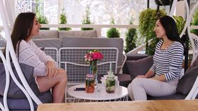 Two cheerful girls are chatting and having fun during sitting at cafe. Three cheerful girls are chatting and having fun during sitting at cafe. Friends are spend stock footage