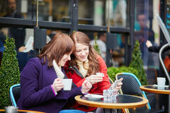 Two cheerful girls drinking coffee in a Parisian street cafe Stock Photography