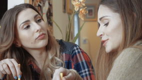 Two cheerful girls drinking smoothie and gossiping. Two beautiful young girl having conversation at home. Relaxing time of two pretty friends stock video footage
