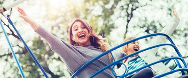 Two cheerful girls enjoying their ride at the amusement park Stock Photo