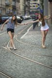 Two cheerful girls friend walked together through street. Travel. Two cheerful girls friend walked together through street Royalty Free Stock Photography