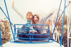 Two cheerful girls having fun on merry go round. At amusement park Royalty Free Stock Photography