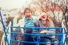 Two cheerful girls having fun on merry go round. At amusement park Royalty Free Stock Photo