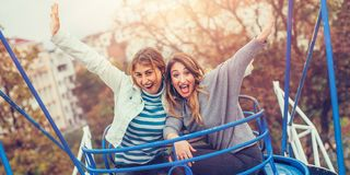 Two cheerful girls having fun on merry go round. Two beautiful cheerful girls enjoying their ride at the amusement park Stock Image