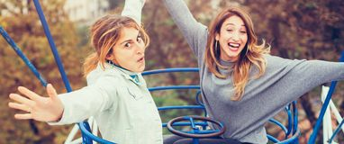 Two cheerful girls having fun on merry go round. At amusement park Royalty Free Stock Photos
