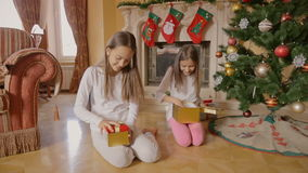 Two cheerful girls in pajamas sitting under Christmas tree and opening boxes with presents stock footage
