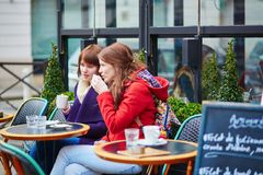 Two cheerful girls in a Parisian street cafe Stock Photo