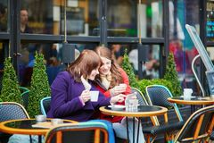 Two cheerful girls in a Parisian street cafe Stock Image