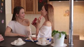Two cheerful girls prepare breakfast at home. Two cheerful girls prepare breakfast at home in the kitchen, they cut a vegetable salad and sing into sausage as stock footage