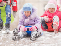Two cheerful girls are rolling hills with each other with icy hill. Two girls in the winter ride on a snowy hill surrounded by other children Stock Photos