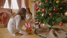 Two cheerful girls running from the house second floor to the living room to open Christmas gifts. Two cheerful girls running from the house second floor to stock video