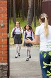 Two cheerful girls running to home after school royalty free stock photos