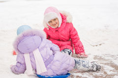 Two cheerful girls slid down the icy hill. Two girls in the winter ride on a snowy hill surrounded by other children Royalty Free Stock Images