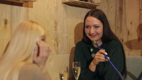 Two cheerful girls smoke hookah in cafe. stock footage
