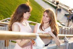 Two cheerful girls stand on the stairs. On embarkment Royalty Free Stock Images
