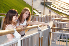 Two cheerful girls stand on the stairs. On embarkment Royalty Free Stock Photography