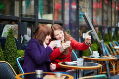 Two cheerful girls taking selfie in a Parisian cafe Royalty Free Stock Photography