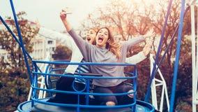 Two girls taking selfie while having fun in amusement park. Two cheerful girls taking selfie while riding on merry go round in amusement park Stock Images