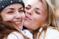 Two cheerful girls twins. In the street Stock Photos