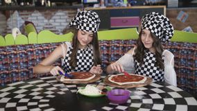 Two cheerful girls in uniform cooking a pizza on master class in cafe 4K. Two cheerful girls in uniform cooking a pizza on master class of chief in cafe. 4K stock video