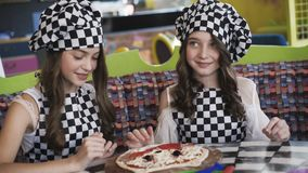 Two cheerful girls in uniform cooking a pizza on master class in cafe 4K. Two cheerful girls in uniform cooking a pizza on master class of chief in cafe. 4K stock video footage