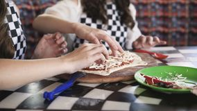 Two cheerful girls in uniform cooking a pizza on master class in cafe 4K. Two cheerful girls in uniform cooking a pizza, putting a sausage on dough on master stock video
