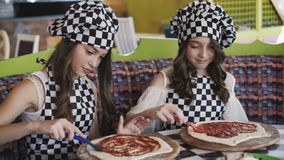 Two cheerful girls in uniform cooking a pizza on master class in cafe 4K. Two cheerful girls in uniform cooking a pizza, oiling dough with tomato sauce on master stock video footage