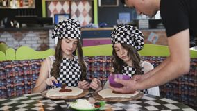 Two cheerful girls in uniform cooking a pizza on master class in cafe 4K. Two cheerful girls in uniform cooking a pizza, oiling dough with tomato sauce on master stock video