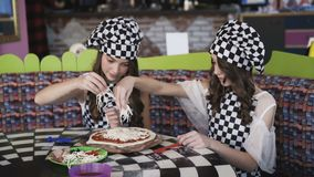 Two cheerful girls in uniform cooking a pizza on master class in cafe 4K. Two cheerful girls in uniform cooking a pizza, strewing cheese on dough on master class stock video